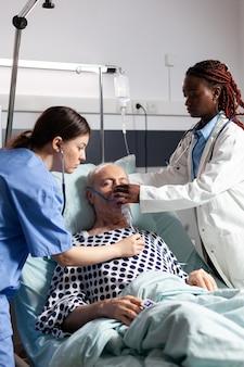 Médecin africain et assistant médical aidant un homme âgé à respirer