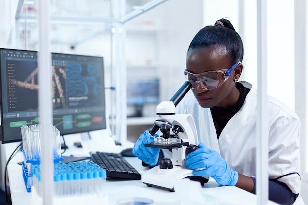 Médecin africain en pharmacologie à la recherche d'un signe de patoloy dans un échantillon de patient à l'aide d'un microscope. scientifique noir de la santé dans un laboratoire de biochimie portant un équipement stérile.