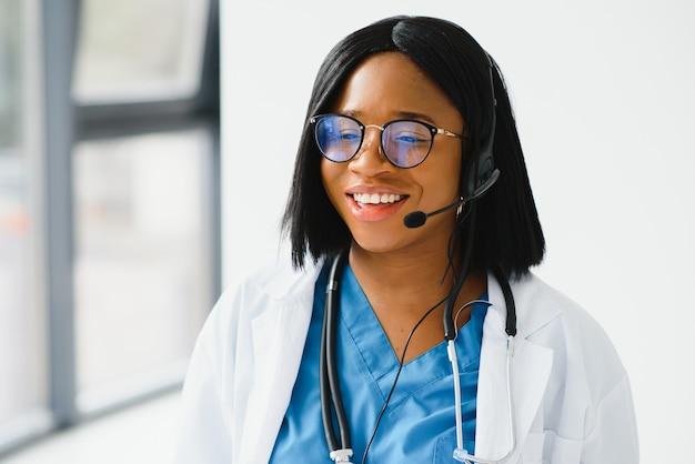 Médecin africain porter un casque consulter une patiente noire faire un appel vidéo webcam en ligne sur un ordinateur portable