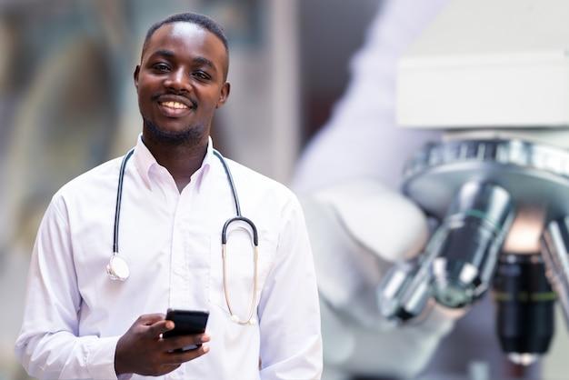 Médecin africain tenant un smartphone et un stéthoscope avec laboratoire de microscope