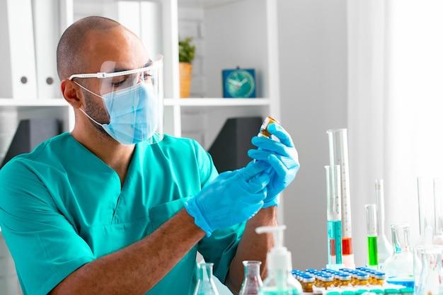 Médecin afro-américain assis à la table et se prépare à faire une injection d'un médicament