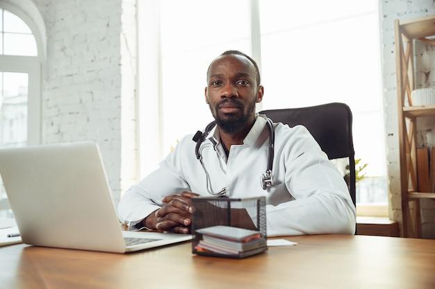 Médecin afro-américain consultant pour un patient travaillant au cabinet