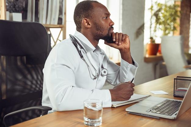 Médecin afro-américain consultant pour un patient travaillant dans un cabinet en gros plan