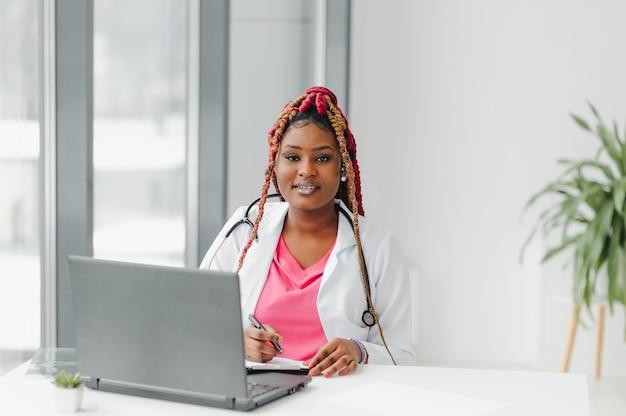 Médecin afro-américain dans le casque de consultation avec le patient au cours de l'appel téléphonique