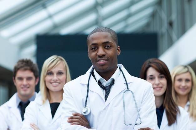 Un médecin afro-américain dirige son équipe avec les bras croisés