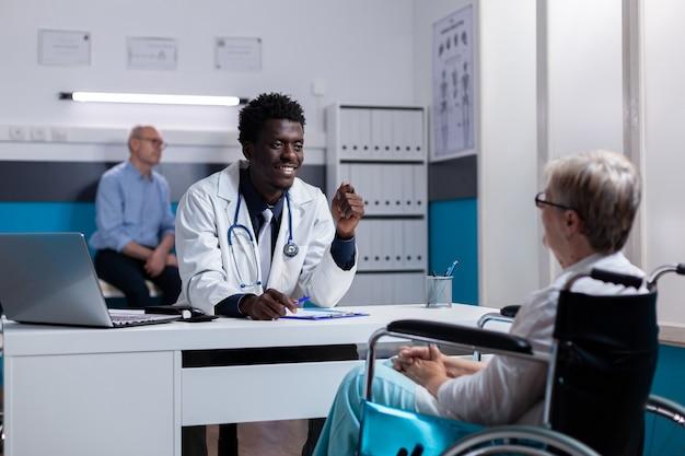 Médecin afro-américain expliquant le diagnostic à une vieille femme handicapée