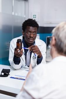 Médecin afro-américain montrant un pot de pilules de guérison