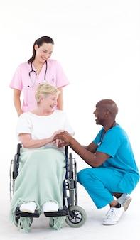Médecin afro-américain parlant à un patient dans une chaise roulante
