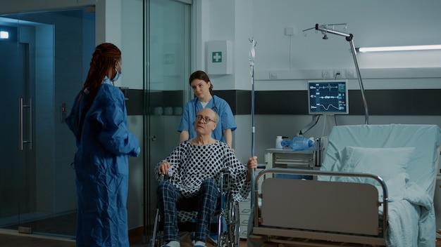 Médecin afro-américain prenant un patient malade en fauteuil roulant