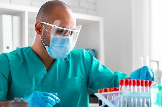 Médecin afro-américain ou travailleur de laboratoire examine un échantillon de sang en clinique