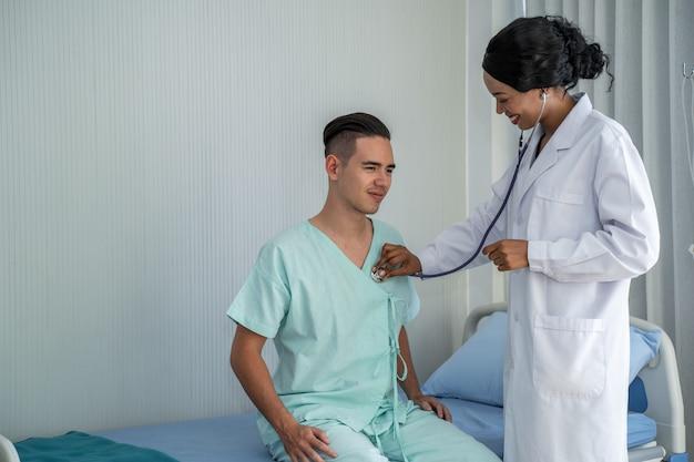 Le médecin afro-américain vérifie les symptômes en vérifiant le cœur du patient sur le lit du patient. et fournir une consultation concernant le traitement aux patients assis dans un fauteuil roulant