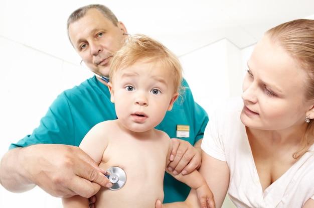 Un médecin d'âge moyen en blouse verte écoute le dos d'un bébé lors d'une étude médicale