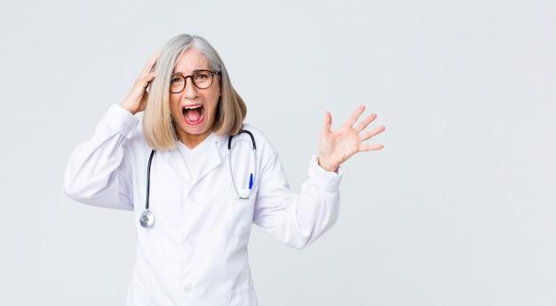Médecin d'âge moyen femme riant, l'air heureux, positif et surpris, réalisant une excellente idée pointant vers latéral