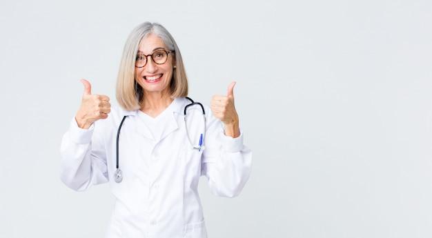 Médecin d'âge moyen femme souriant largement à la recherche de bonheur, positif, confiant et réussi, avec les deux pouces vers le haut