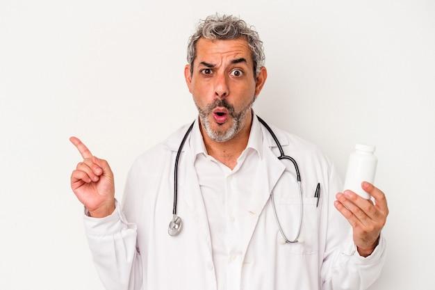Médecin d'âge moyen homme caucasien isolé sur fond blanc pointant vers le côté