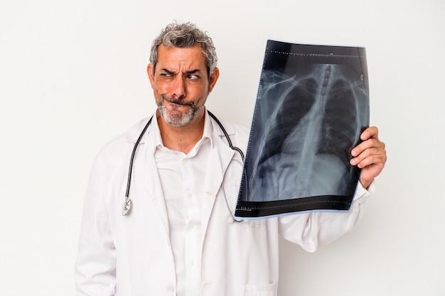 Médecin d'âge moyen homme caucasien tenant une radiographie isolée sur fond blanc confus, se sent dubitatif et incertain.