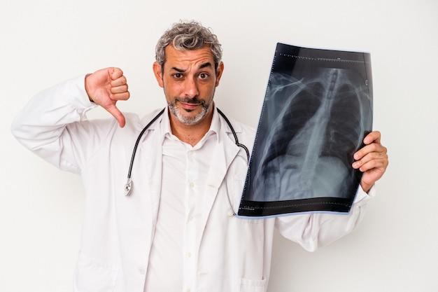 Médecin d'âge moyen homme caucasien tenant une radiographie isolée sur fond blanc montrant un geste d'aversion, les pouces vers le bas. notion de désaccord.
