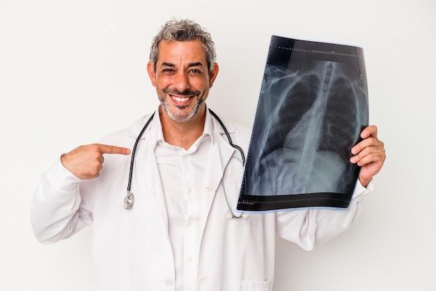 Médecin d'âge moyen homme caucasien tenant une radiographie isolée sur fond blanc personne pointant à la main vers un espace de copie de chemise, fier et confiant