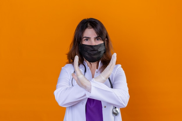 Médecin d'âge moyen portant une blouse blanche dans un masque facial de protection noir et avec un stéthoscope croisant ses mains