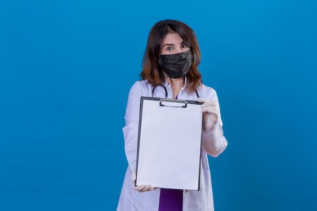 Médecin d'âge moyen portant une blouse blanche dans un masque facial de protection noir et avec un stéthoscope montrant le presse-papiers