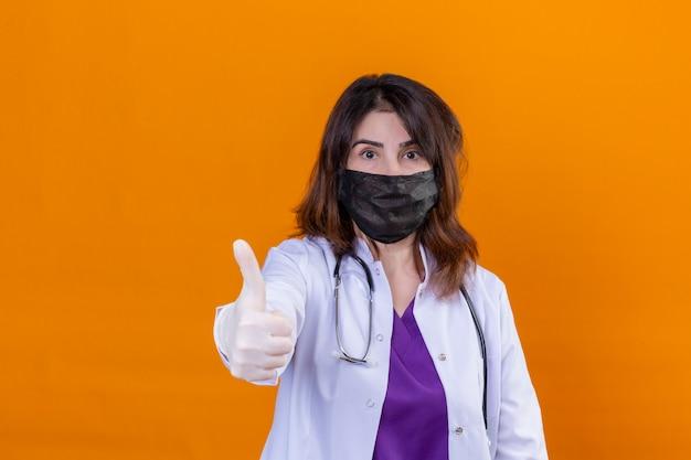 Médecin d'âge moyen portant une blouse blanche en masque facial protecteur noir et avec stéthoscope positif et heureux montrant les pouces vers le haut sur le mur orange