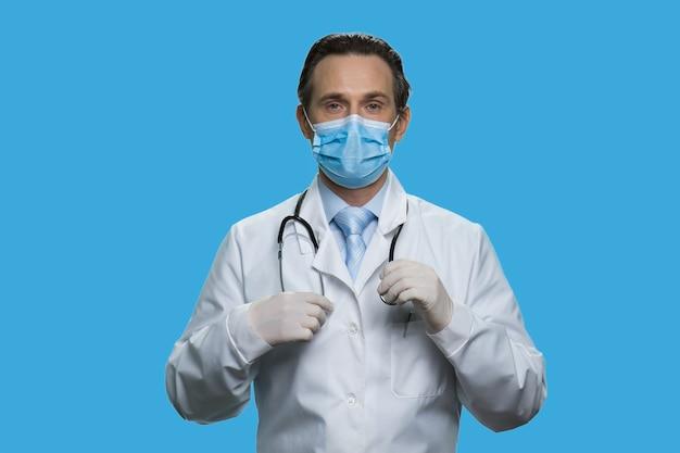 Un médecin d'âge moyen sérieux porte un stéthoscope. médecin en blouse blanche et masque de protection isolé sur fond bleu.