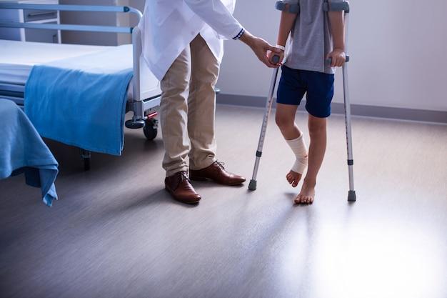 Médecin aidant un garçon blessé à marcher avec des béquilles