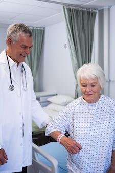 Médecin aidant un patient senior en salle