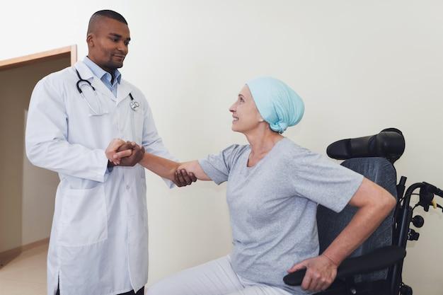 Un médecin aide une femme en rééducation après un cancer.