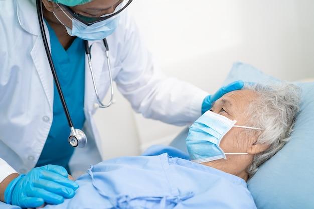 Un médecin aide une patiente asiatique âgée portant un masque facial à l'hôpital pour protéger le coronavirus
