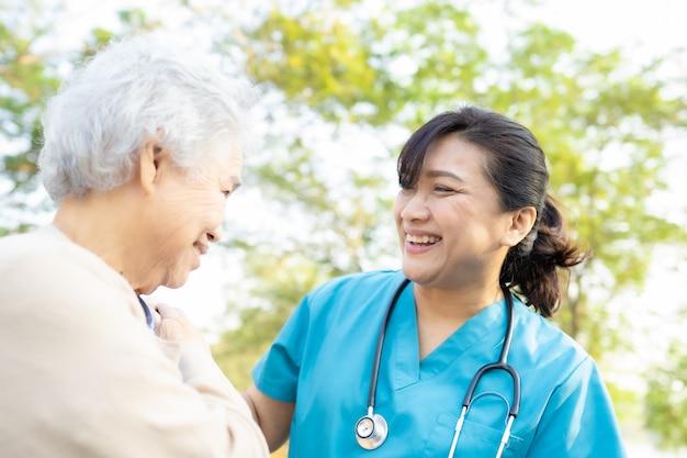 Médecin aide et soins femme senior asiatique marchant au parc.