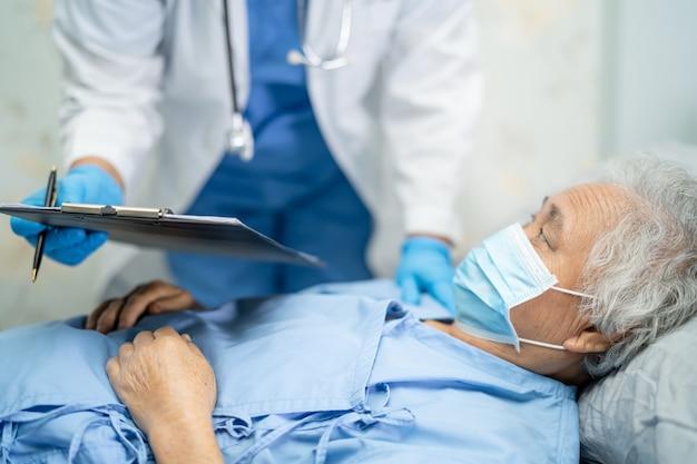Médecin à l'aide d'un stéthoscope pour vérifier la patiente asiatique senior pour protéger l'infection covid coronavirus