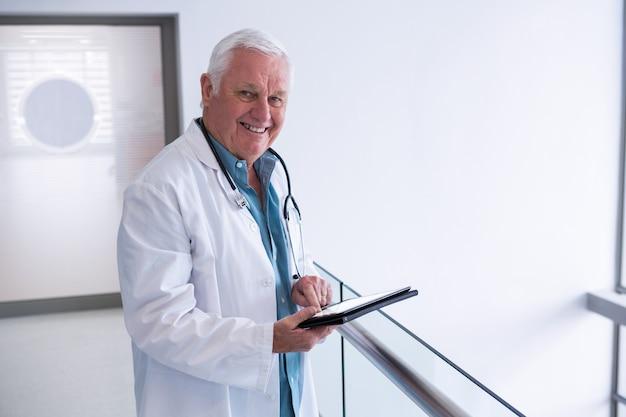 Médecin à l'aide d'une tablette numérique dans le passage à l'hôpital