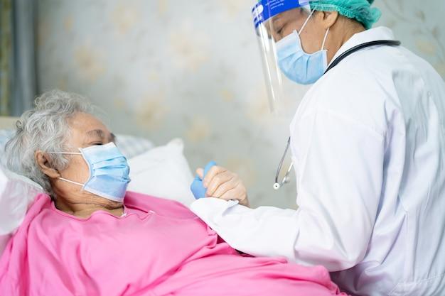 Un médecin aide et vérifie une patiente asiatique âgée ou âgée portant un masque facial à l'hôpital pour protéger l'infection covid-19 coronavirus.