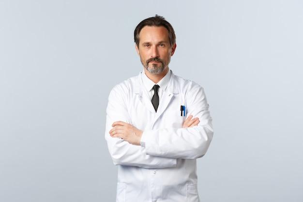 Médecin à l'air sérieux en blouse blanche sur la poitrine des bras croisés, l'air confiant.