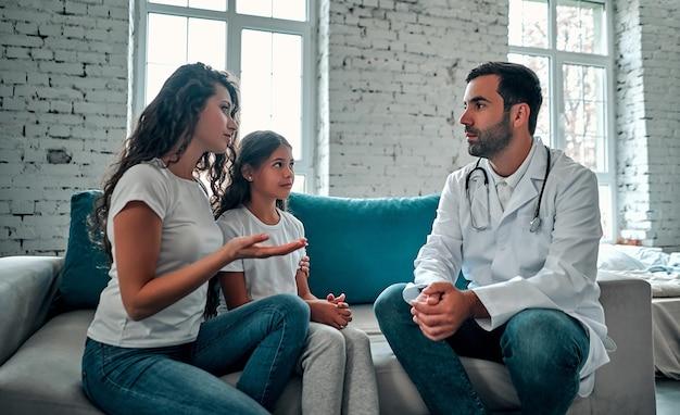 Médecin américain parlant au jeune enfant et à sa mère.