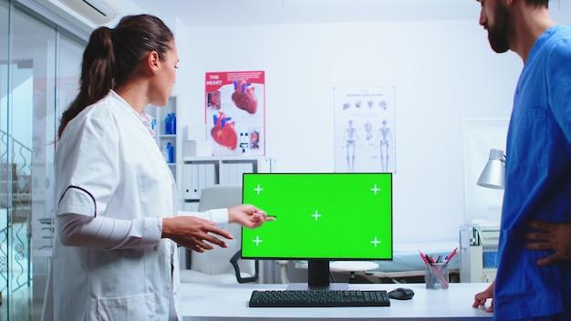 Médecin analysant les résultats des patients avec un assistant sur ordinateur avec écran vert à l'hôpital. medic portant une blouse blanche dans une clinique pointant sur le bureau avec une clé chroma parlant avec une infirmière sur le diagnostic du patient