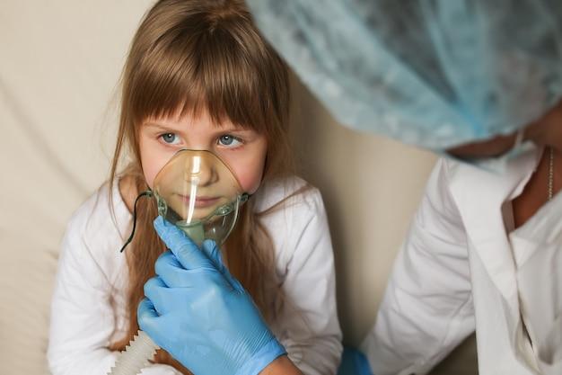 Médecin appliquant un traitement par inhalation de médicaments sur une petite fille