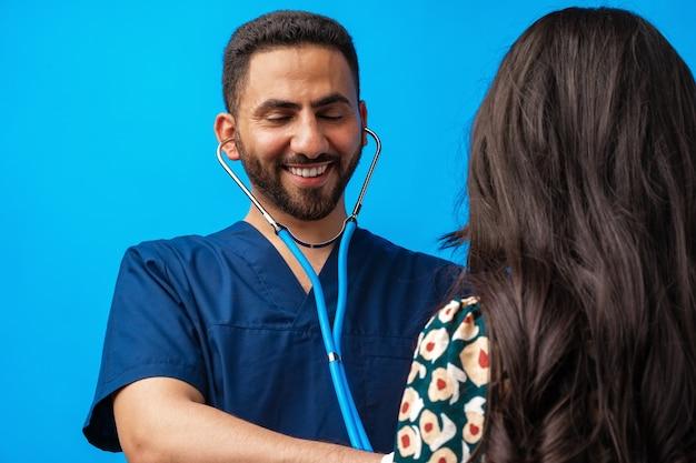 Médecin arabe en uniforme bleu debout avec le stéthoscope et écoutant le rythme cardiaque d'une femme...