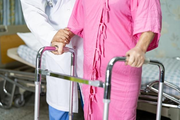 Un médecin asiatique aide et soutient une patiente âgée à pied avec un marcheur à l'hôpital