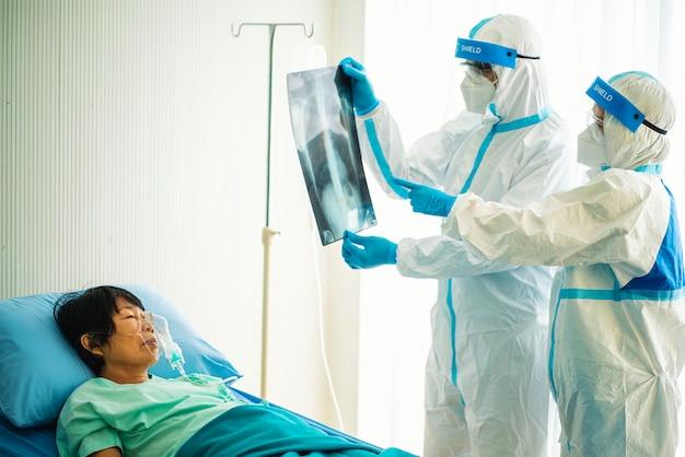 Médecin asiatique en équipement de protection individuelle ou epi regardant un film radiographique d'un patient infecté par le covid-19 ou un coronavirus à l'hôpital.