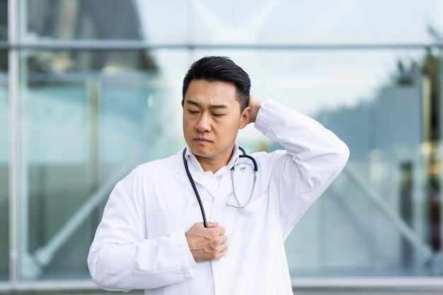 Un médecin asiatique est fatigué après le travail, déprimé et déçu du travail effectué dans la rue près de la clinique