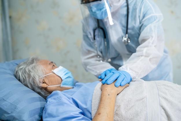 Médecin asiatique portant un écran facial et une combinaison epi pour vérifier que le patient protège le coronavirus covid-19.