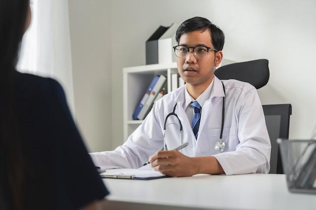 Un médecin asiatique rapporte les symptômes et conseille le patient.