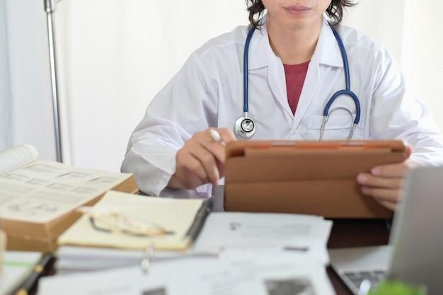 Médecin asiatique recherchant la lecture de livres médicaux et de connaissances en ligne