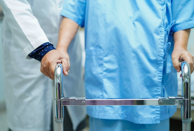 Un médecin asiatique soigne, aide et soutient une patiente âgée.