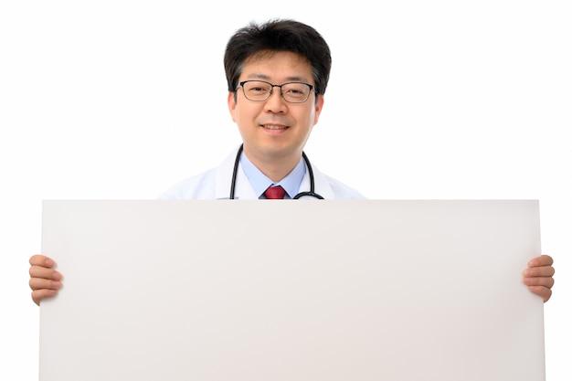 Un médecin asiatique tenant un babillard vierge.