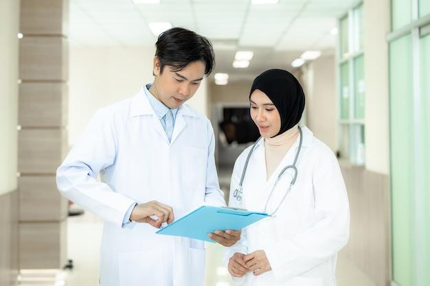 Médecin asiatique tenant le presse-papiers et femme musulmane