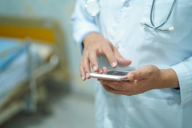 Médecin asiatique tenant un téléphone numérique.