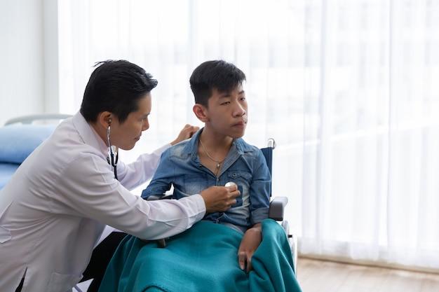 Un médecin asiatique utilise un stéthoscope pour contrôler un patient en fauteuil roulant
